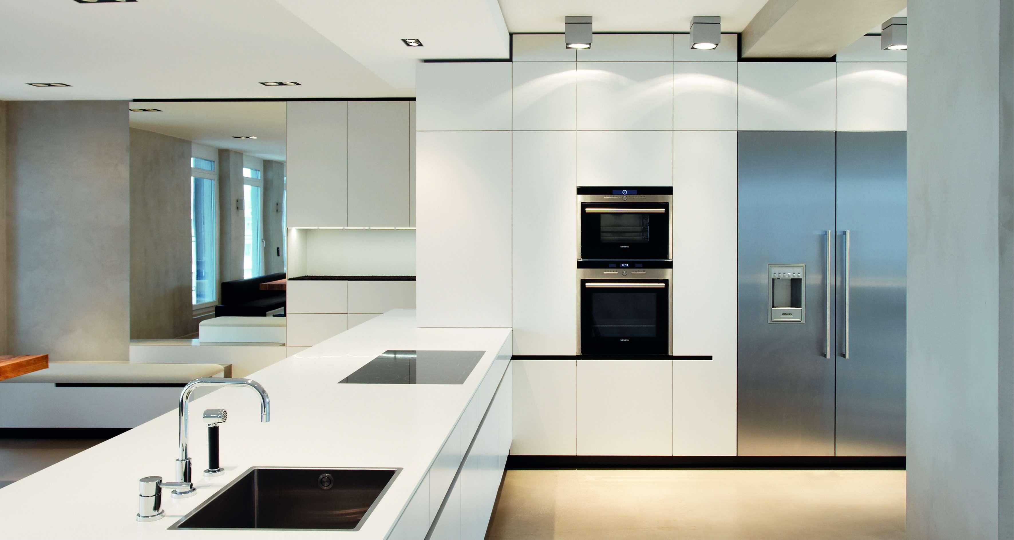 Großzügige und freistehende Küche in Lack Weiß, grifflos mit Kücheninsel und sehr großem Kühlschrank.