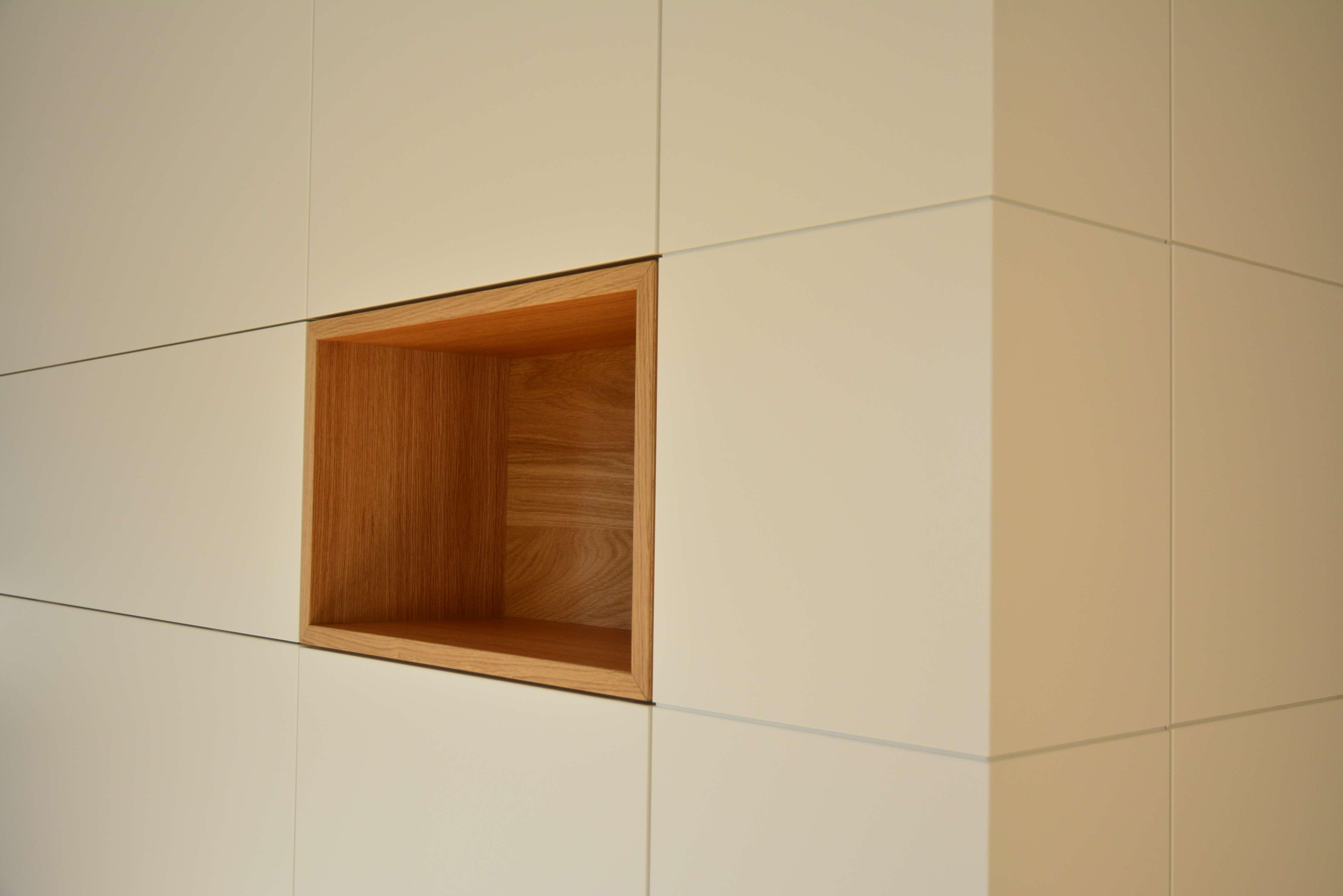 Einbauschrank in weiß mit würfelförmiger Aussparung, die mit Holz ausgebaut ist. Kubus in Möbel integriert.