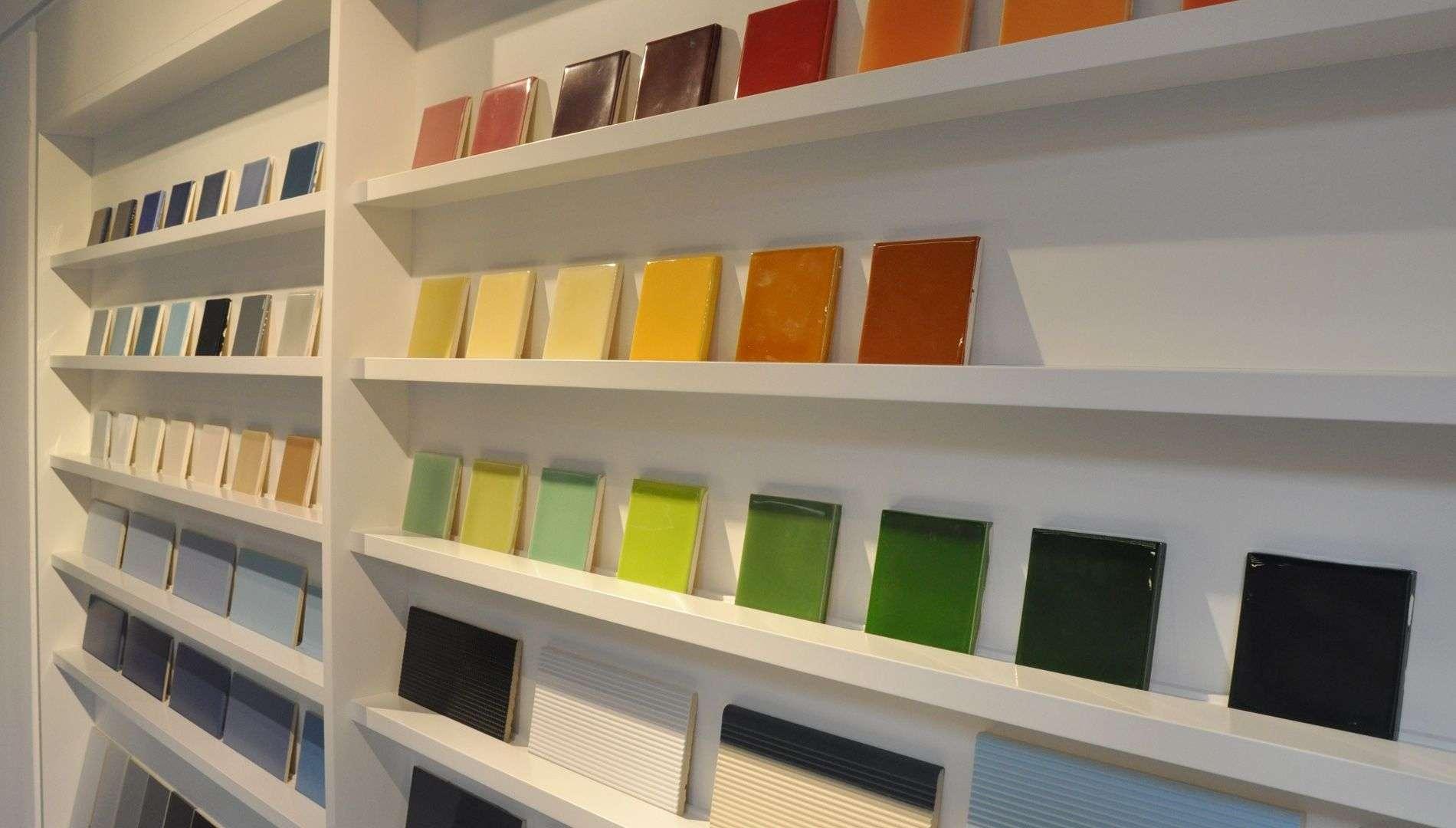 Ausstellungsfläche für Fließen in einem Wandschrank, wie Zeitungsauslage. Viele bunte kleine Muster-Fließen in Regal zur Übersicht drapiert.