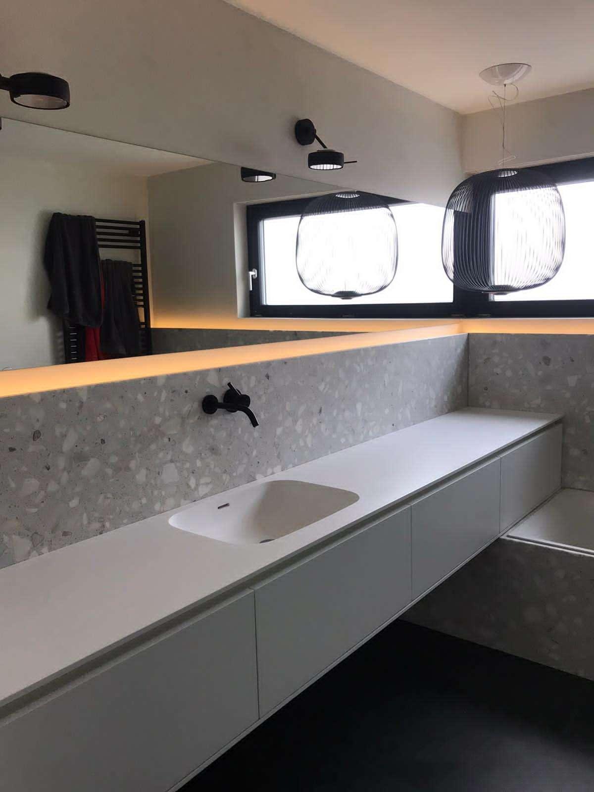 Freihängendes Badezimmermöbel mit fugenlosem Corian Waschtisch. Spiegelband über die Breite des Raums. Wasserhahn aus der Wand kommend.