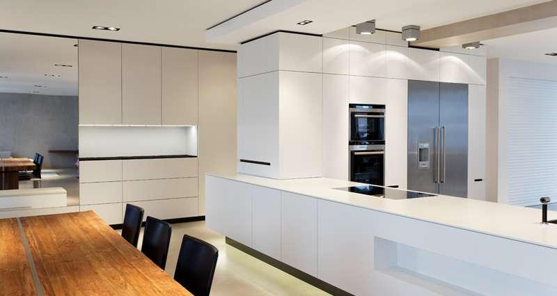 Loft Küche mit viel Schrankfläche und mit sehr großem Küchenblock. Daneben der Esstisch aus Naturholz.