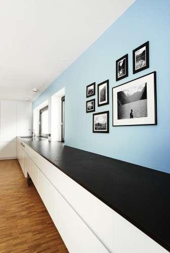 Lange, geradlinige Küchenzeile in weiß, grifflos und mit schwarzer Stein-Arbeitsfläche. Hellblaue Wand dahinter an der Bilder hängen.