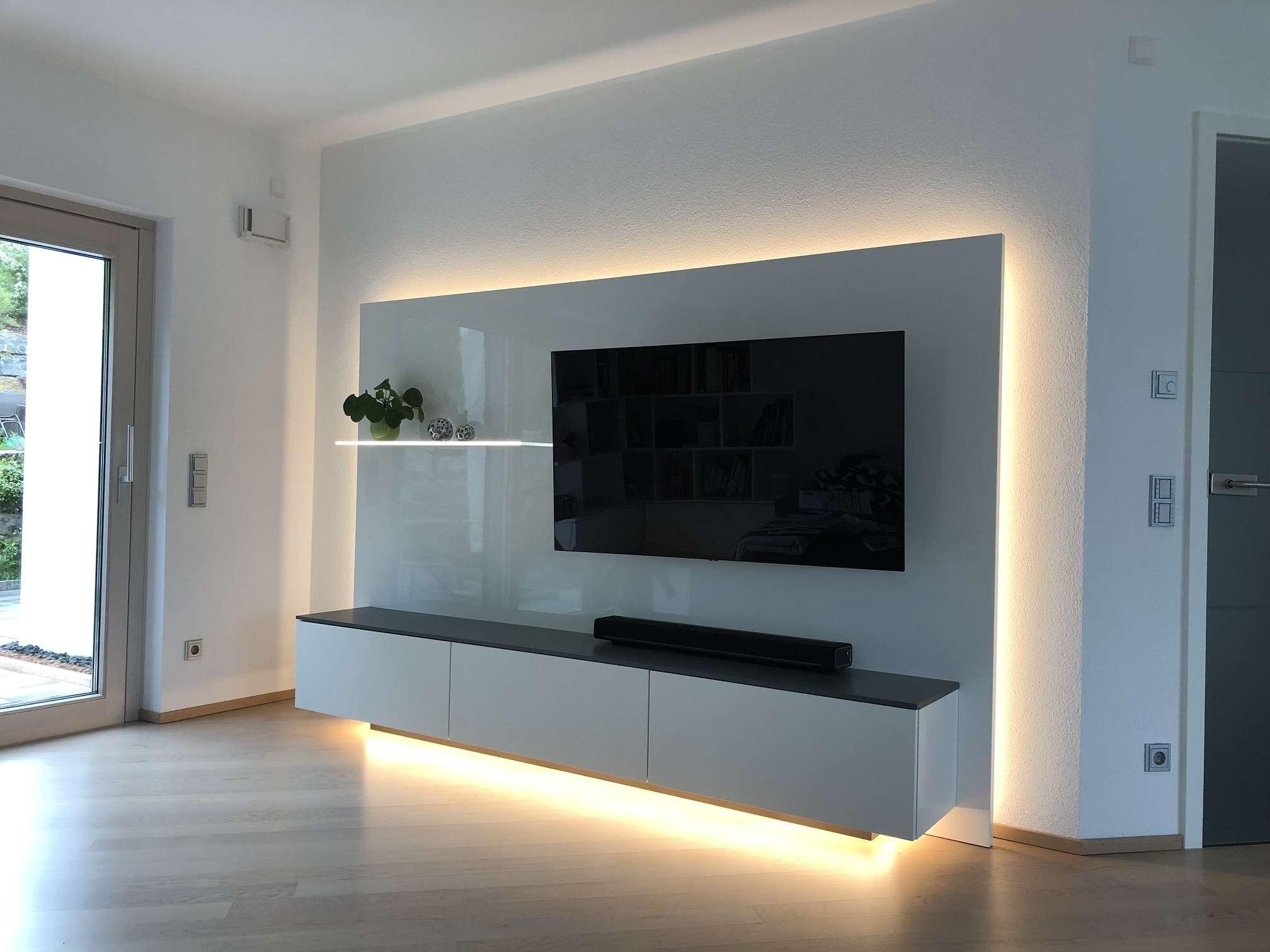 Fernsehmöbel in Glanzlack weiß mit indirektem Licht außenrum, das von hinten strahlt. Rückwand mit niedrigem Sideboard für Stauraum.