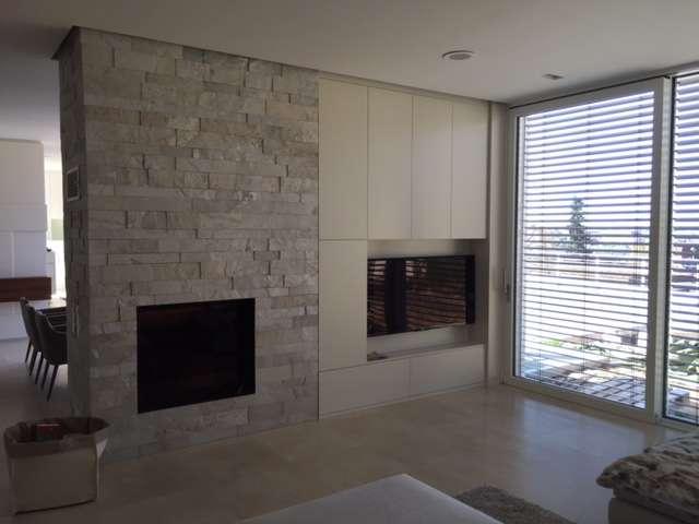 Wohnzimmermöbel zwischen Kamin und Terassentür in weiß, grifflos und mit integriertem Fernseher.